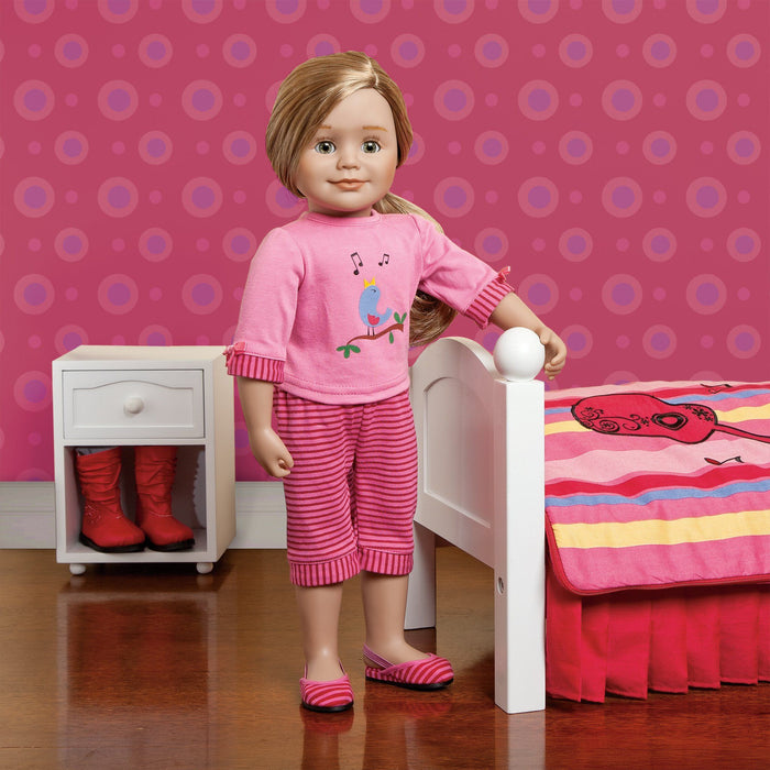 Two-piece pajamas with slippers shown on 18 inch doll Léonie with Maplelea bedding and night table.
