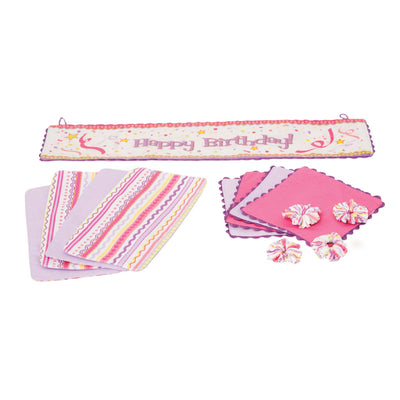 Set to Celebrate fabric pieces, including 4 pink and purple placemats, 4 patterned napkins, 4 napkin holders, and 1 bilingual birthday banner for all 18 inch dolls.