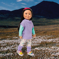 Casual outfit feather watercolour pattern tights, mint green long-sleeve tee, purple tunic sweater and leg warmers with pink feather hairband fits all 18 inch dolls. Shown on a Nunavut background.
