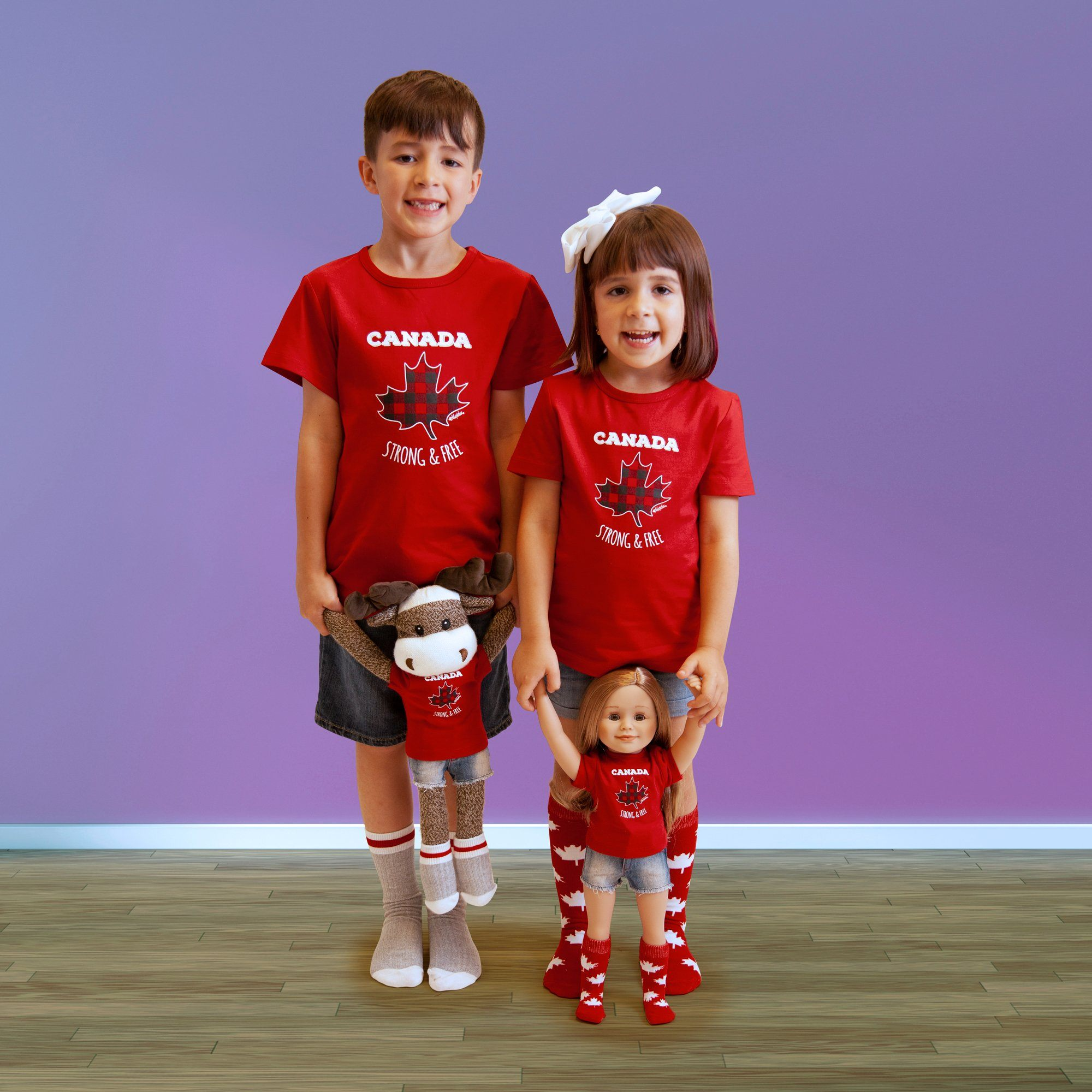 Boy, girl, doll and stuffed moose wearing matching Canadian socks.