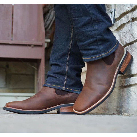 Man Wearing Brown Chelsea Ankle Boots with blue jeans