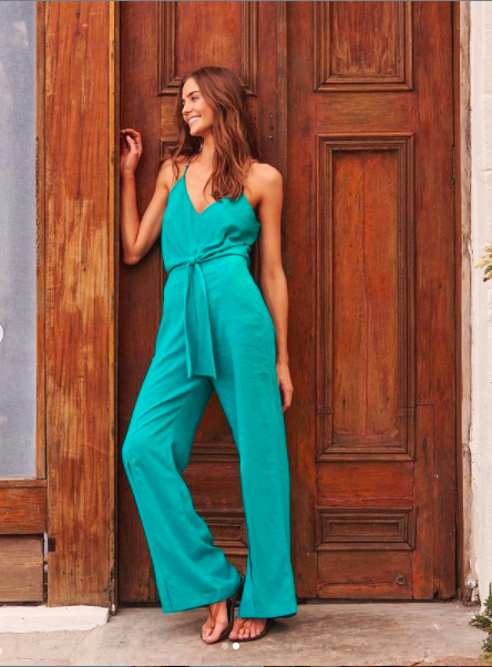 Model wearing turquoise jumpsuit