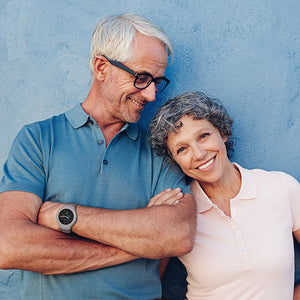 Smiling couple facing camera, with Spacetalk Life being worn on the wrist of man in t-shirt