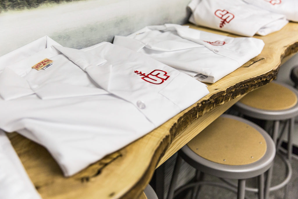 White lab jackets with our red Up Cannabis logo that are worn at our Brantford facility.