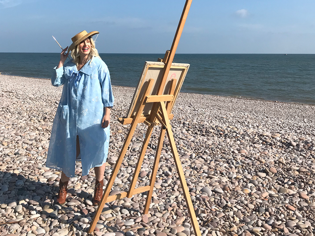 Influencer and blogger Jenny Mandera stands on a pebble beach on a bright sunny spring day. She is posed playfully at an easel, paintbrush in hand, and smiles into the middle distance, clutching her straw hat to her head against the sea breeze. She wears a distinctive blue swing coat  - an original vintage coat from the fifties.