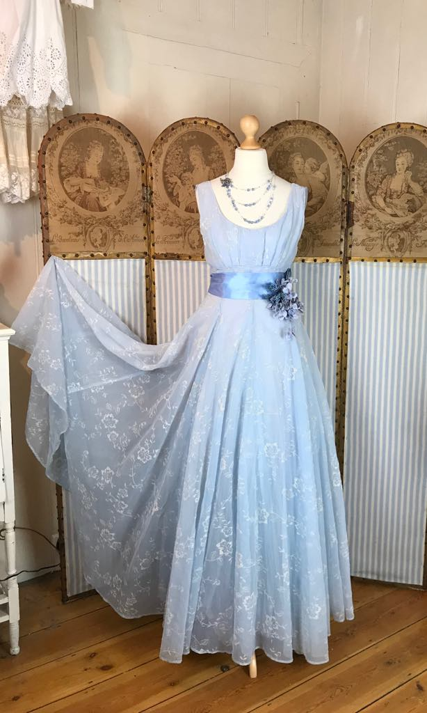 original authentic vintage 1950's blue organza full length empire line ball gown with a boat neckline, blue satin sash and pink corsage.