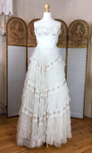 An original vintage 1950's strapless wedding dress in ivory and pink lace is shown inside a wedding dress shop