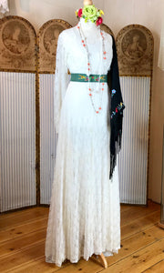 1940's lace wedding dress with long slevves, styled with a nod to Frida Kahlo with a colourful flower crown, boho beads and a green embroidered sash