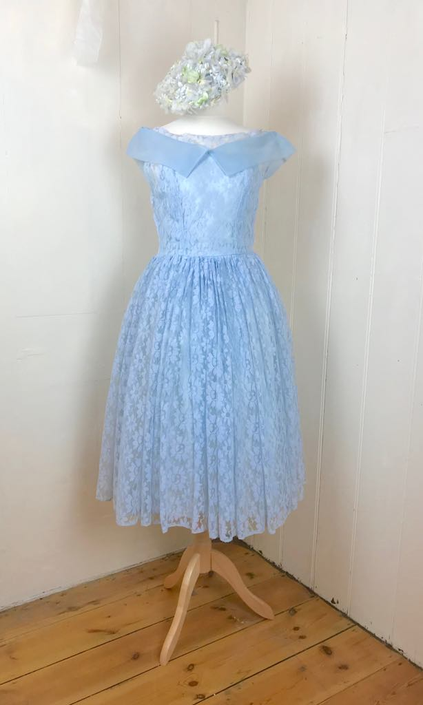 A pale blue vintage lace dress from the 1950's is shown on a dressmakers dummy, with a hat made of silk hydrangeas
