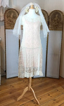 a front on shot of a stunning lace nineteen twenties wedding dress with a dropped waist