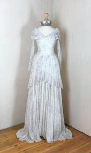Shimmering vintage wedding gown in ivory lace with silver pewter threadwork, with a shawl collar , pelmet train and long sleeves