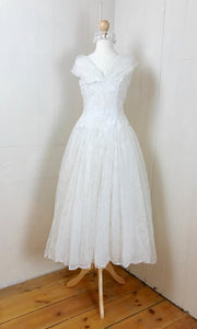 A simple yet elegant ivory wedding dress with a full circle skirt , original 1950's vintage dress