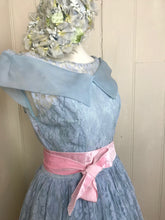 A pale blue vintage dress with a wide collar and a pink sash makes a charming picture on a vintage dummy. The details of the lace pattern can be clearly seen.