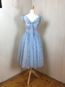 An elegant bow detail graces the back of an original 1950's pale blue prom dress with a nipped in waist and circle skirt
