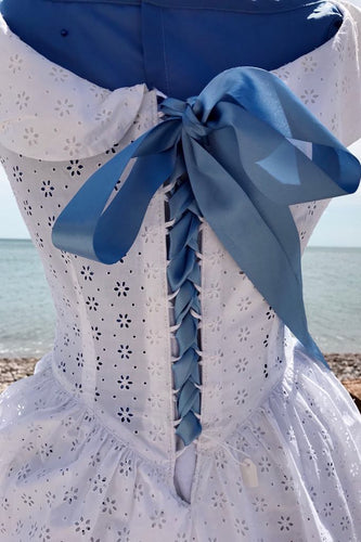 A crisp white broderie anglais dress is laced up the back with a blue satin ribbon, corset style. Around the nipped in waist, you can just glimpse a pebble beach and the sea beyond.