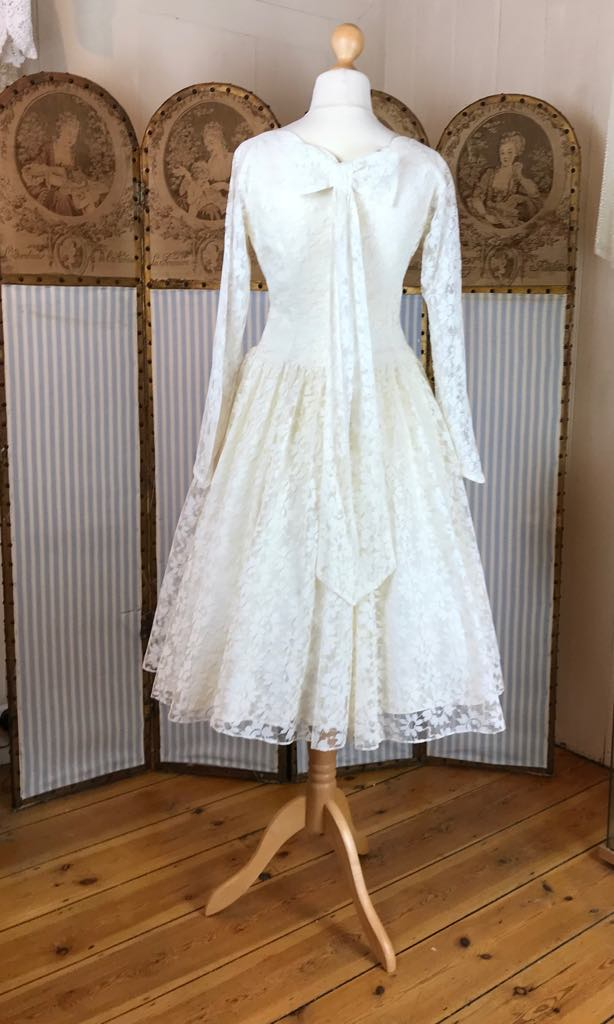 The back of a 1950's wedding dress in ivory lace with a beautiful bow detail
