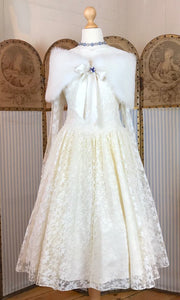 A 1950's wedding dress is shown with a feathered cap and blue paste brooch and necklace. The dress is a prom dress shape.