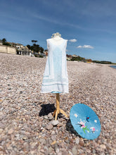 A beautiful white vintage sundress is shown on a beach