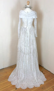 The back of a 1950's wedding dress in ivory lace with silver threadwork. the back view shows the beautiful lace train