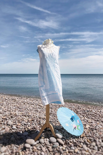 a simple white lawn mini dress with a high neck and drawn thread lace is shown worn on a pebble beach. A parasol is resting on the ground.