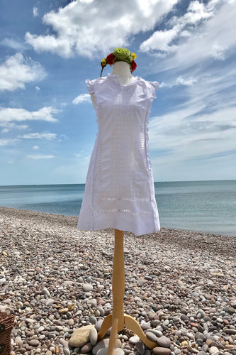 A crisp white linen mini dress and colourful flower crown are shown on a shop dummy with a pebble beach in the background.