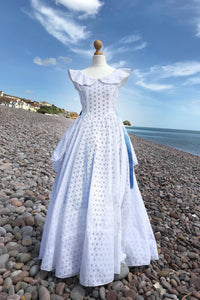 A crisp white cotton dress, full length with a nipped in waist and circle skirt , is shown on a dressmakers dummy on a sunny pebble beach. Blue ribbons flutter at the waist