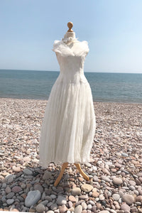 beautiful vintage wedding dress in ivory flocked organza, photographed on a pebble beach