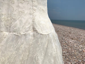 The scalloped waist of fifties wedding dress in ivory flocked organza