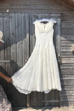 A 50's prom dress in ivory is shown hanging on a beach hut door. A woman is holding the skirt out to show the fullness.