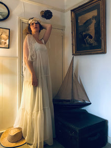 A model is shown in a vintage interior wearing a floor length 1970's flowing white dress in a grecian style with fringed sleeves. The dress has a high waist and three tiers. She also wears a white paper flower crown