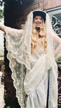 A model with long blonde wavy hair wears a dark hat with a floor length antique lace veil draped over it. She also wears a 1970's flowing wedding dress