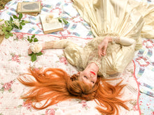 A sleeping red head lies sprawled across a vintage picnic blanket and handmade quilt. A rose falls from her hand. Books land flowers litter the blanket around her. She wears an antique lace and silk wedding gown, created in an Edwardian style. The image feels like something out of Anne of Green Gables