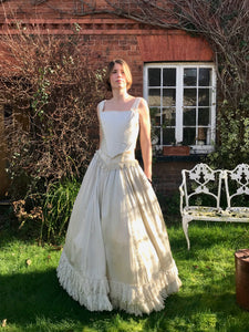 A model wears and antique wedding dress which is in fact two separates - a corset top and full skirt. Both are made from ivory silk. Sunlight dapples the Victorian skirt as the bride stands outside a red brick house.