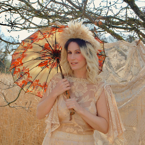 A beautiful art deco parasol with a coral red, jade green and soft gold floral pattern is shown being held by a glamorous blonde model in a seventies laec dress against a field of dry golden grasses. The Pretty antique parasol is made of silk.