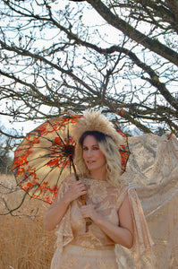A beautiful blonde boho bride wears a dramatic, floor sweeping 1970's wedding dress made with gold lace in a floral pattern. She carries a beautiful vintage parasol which gives a festival feel to the look