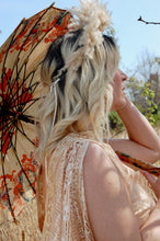 The spokes of a vintage parasol are visible. the parasol is held by boho bride