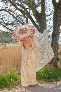 A beautiful boho bride stands on a country lane. She wears a floor sweping, backless vintage lace gown and carries a pretty antique parasol