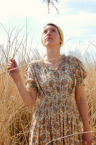 A close up of our model Josie, who looks every inch the glamorous landgirl stood in a field of wheat wearing an original forties dress with a paisley print and a vintage yellow silk headscarf