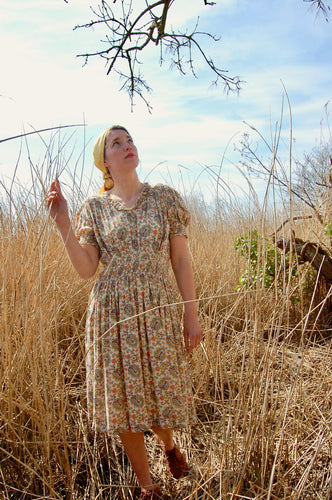 Land girl style! Our model Josie wears a 1940's paisley print summer dress featuring a paisley print, and stands in a field of long, bleached grasses. She has teamed the vintage dress with a vintage silk headdress and flat brown boots.