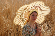 Little house on the prairie style - a pretty girl with a yellow headscarf around her head is framed by a parasol. She wears an original vintage 1940's dress with a paisley print