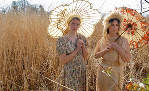 Prairie princesses! Models Josie and Jenny stand in a field of shoulder high golden grasses and reeds. Both carry golden parasols and wear vintage gowns - Josie is in a 1940's summer dress with a paisley print