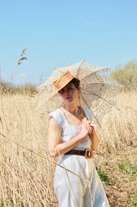 Our model Josie wears an all in one Victorian bloomer set or camobocker in crisp white cotton with a straw hat and parasol. She stands in a field of shoulder high bleached grasses and reeds