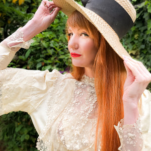 Stunning red headed model in a vintage sunhat and elegant Edwardian lace dress - she's looking out at the camera with a saucy expression.