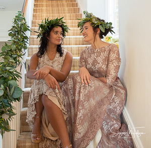 An English country house wedding scene showing two girls in green leaf crowns and vintage lace wedding dresses sat on the sweeping stairs of a charming country house. Country wedding inspiration