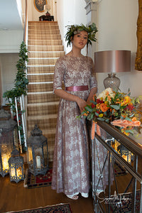 A pretty dark haired model stands in the hallway of a country house, wearing a floor sweeping vintage gown from the 1950's made with a rose patterned lace in an old rose colour.