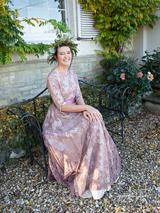 A charming scene - a dark haired white woman sits on a pretty wrought iron bench outside an old stone cottage in devon, wearing a 1950's dress made of lace in an old rose colour and a green leaf crown. Around her, wisteria leaves and dahlias flourish.