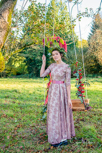 A pretty scene - A dark haired model in a beautiful fifties vintage dress and green leaf crown stands in front of a swing, it's strings twined with flowers. The floor sweeping dress is made of a rose patterned lace in an old rose colour with a deep pink sash. Prom dress wedding inspiration for a bohemian wedding ,