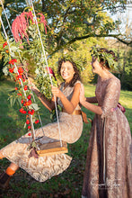 Boho country wedding inspiration - bride and bridesmaid on a floral swing in vintage dresses from Days of Grace. Bohemian flower crowns adorn their dark curls. Vintage bride inspiration with a modern twist