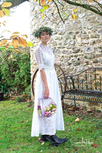 A model wears an original Edwardian wedding gown from days of Grace Vintage. The dress is white cotton lawn, with panels of broderie anglais, haned made lace and hand embroidery, all beautifully worked.