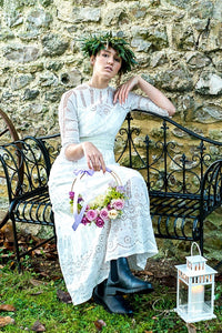 An elegant young woman in a crown of greenery sits on a wrought iron bench. She wears an Edwardian lace wedding dress with broderie and lace panels, a high neck and  elbow length sleeves. She carries a hoop of lilac roses and wears dark boots.